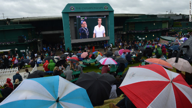 Spectators take shelter under umbrellas on &quot;Murray Mount&quot; for the match between Britain's Andy Murray and Croatia's Marin Cilic.