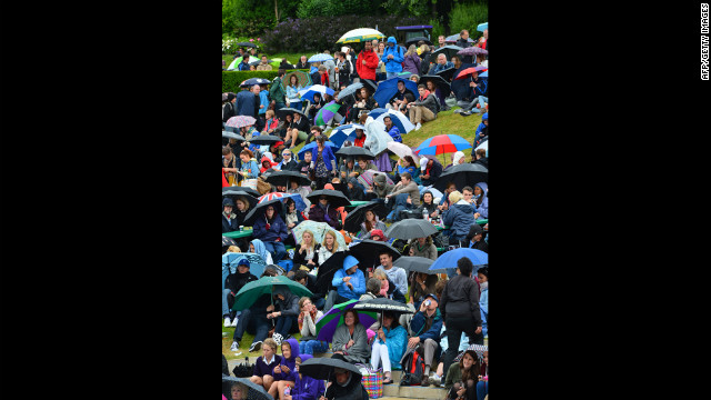 Rain and low temperatures set in again Monday at Wimbledon, delaying some matches and sending fans scurrying for cover.