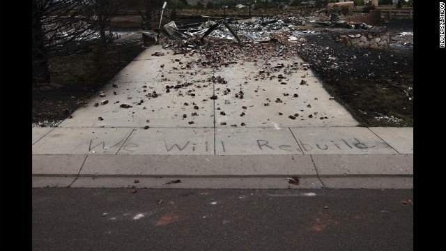 The words &quot;We Will Rebuild&quot; are seen written on the sidewalk in front of a house in Colorado Springs that was destroyed by the fire.