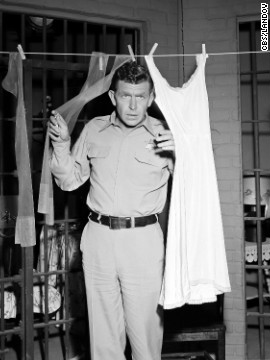 "Griffith as Sheriff Andy Taylor peers through laundry in ""Andy and the Woman Speeder."""