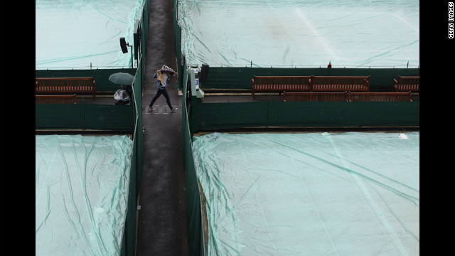 A spectator walks between the outside courts during rain delays on Monday.