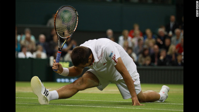 Viktor Troicki of Serbia slips while hitting a return shot against Novak Djokovic of Serbia on Monday.