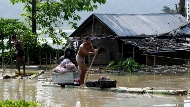 A villager moves his belongings on a banana raft from his half submerged house in floodwaters at Mayong village in Morigoan district on June 28. Prime Minister Singh has committed $90 million for relief effort.