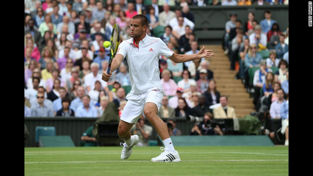Mikhail Youzhny of Russia hits a backhand return during his men's singles quarterfinal match against Roger Federer of Switzerland.