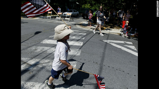 A boy runs while twirling American flags in the Takoma Park, Maryland, parade.