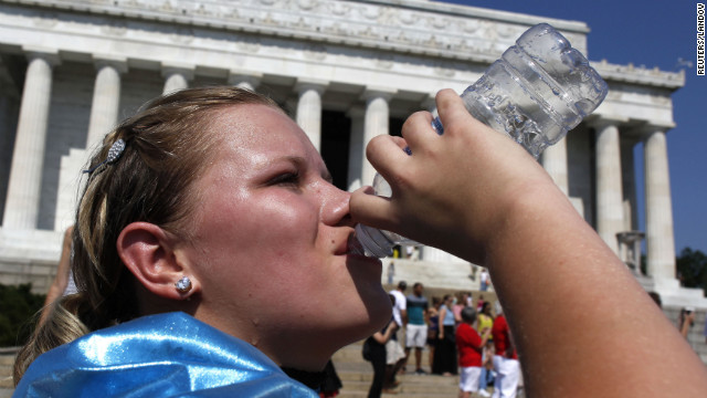 Abbi Buck, of Cookeville, Tennessee, gulps a bottle of water as sweat drips down her face as she visits the Lincoln Memorial in Washington on Tuesday.