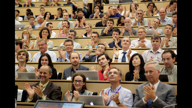 Attendees at the seminar applaud as physicists explain recent findings about a never-before-seen subatomic particle called the Higgs boson.