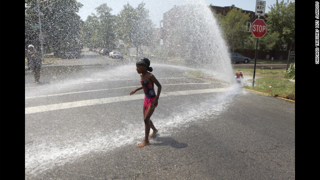 Keshyra Pitts, 7, plays in the spray of a hydrant in Chicago on Wednesday.