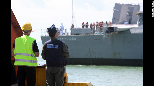 Investigators from France and Brazil wait for the Brazilian Navy frigate to unload the tailfin of the air bus.