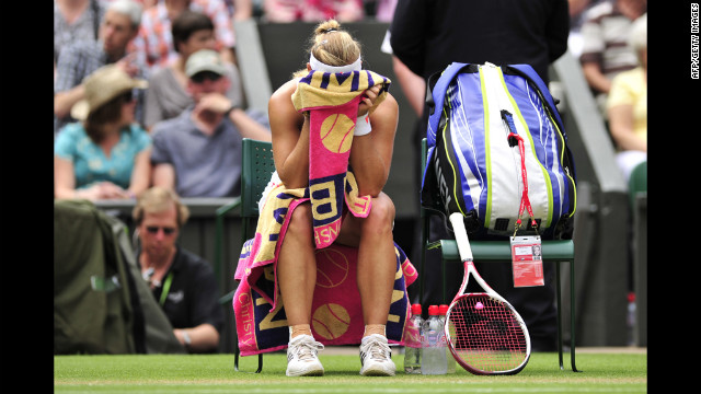 Kerber buries her head in her towel during a break between games in her Ladies' Singles semifinal defeat to Radwanska.