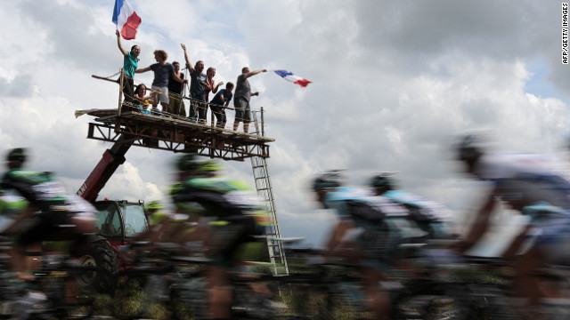 Fans wave French flags and cheer on riders Thursday as the main group passes on the way from Rouen, where Stage 5 of the race started, to Saint-Quentin.