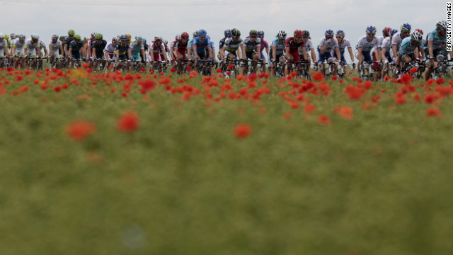 Riders pass a field of poppies as they race through the French countryside Thursday.