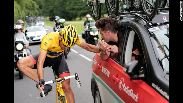 Fabian Cancellara of team RadioShack-Nissan holds on to the team car as he makes an adjustment during the race Thursday.