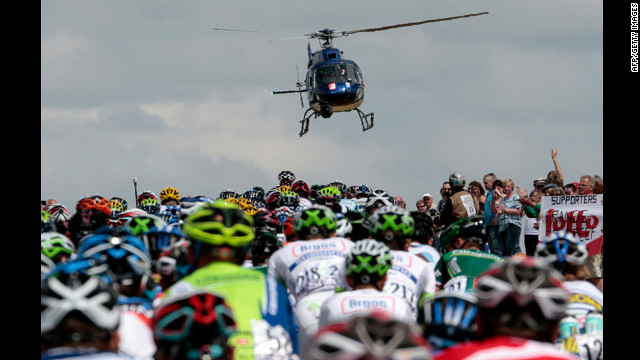 Fans cheer and a television helicopter flies above as the riders stream by.