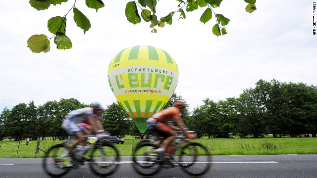 Riders roll past a hot-air balloon sitting in a field along Thursday's course.