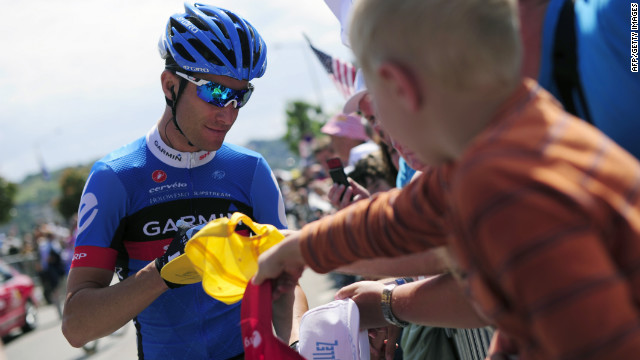 Christian Vande Velde of the Garmin-Sharp team signs an autograph for a fan before the beginning of Thursday's stage.