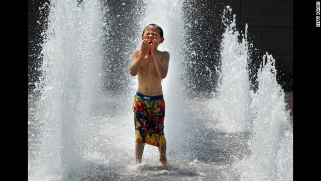 Six-year-old Spencer Hwang-Geddes of Ithaca, New York, cools off at the Yards Park on Thursday. Weather forecast predicted the hot weather will last through Sunday with possible daily triple-digit temperatures.