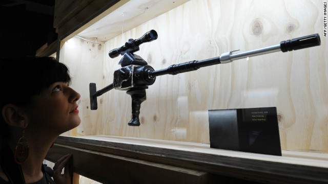 "A woman poses for pictures next to a ""Hasselblad Gun"" used in the film ""Licenced to Kill."""