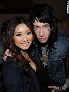 Heavily tattooed and pierced musician Trace Cyrus, pictured with actress Brenda Song (left) attend a party in April in Beverly Hills.