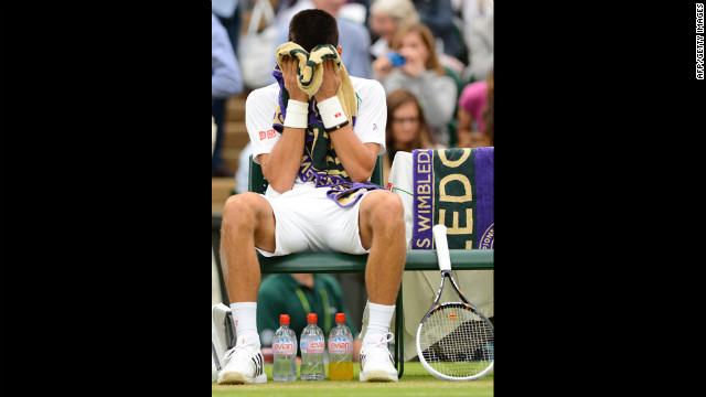 Novak Djokovic buries his head in his towel during a break between games against Roger Federer on Friday.