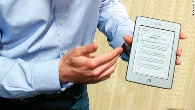 An Amazon employee displays the company's Kindle Touch e-reader last year. Reports say they may be adding a smartphone.