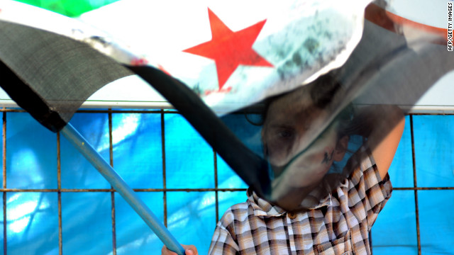 A Syrian child holds an opposition flag as refugees chant slogans at a refugee camp in Hatay, on July 6, 2012.
