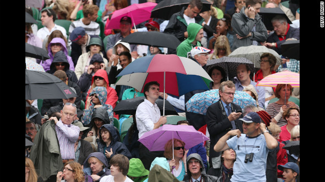 Spectators hide under umbrellas and rain jackets as protection from the rain. See the best WImbledon photos.