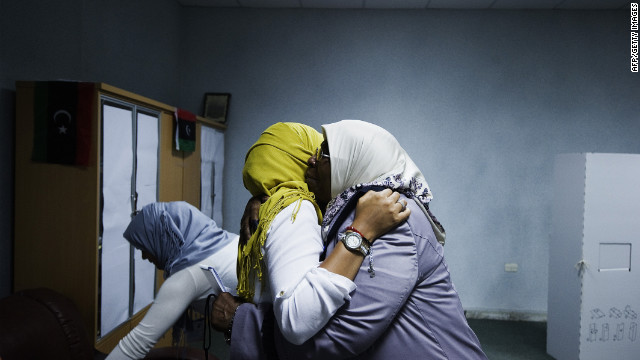 Two Libyan election workers embrace after voting ends at a Tripoli polling station.