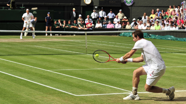 Murray returns a double-handed backhand to Federer during the men's singles Wimbledon championship on Sunday.