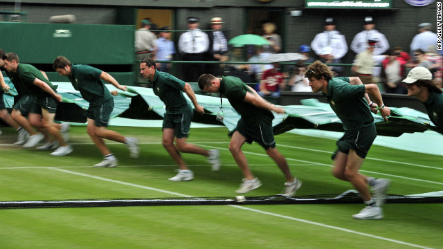 Ground staff pull a cover onto center court during a rain delay in the championship match.