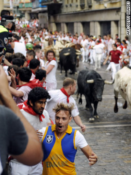Participants seek safety during the first bull run on Saturday.