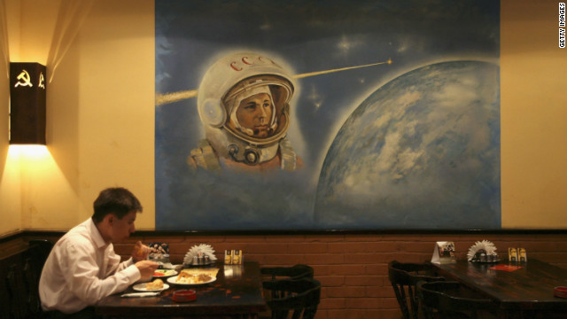 A patron eats under a painting of Yuri Gagarin, the first man in space, in a restaurant decorated with Soviet and communist symbols. Kazakhstan had the world's first spaceport.