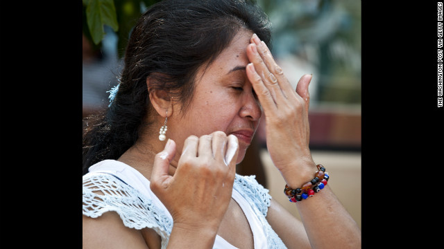 Fatima Domingpe applies sunscreen to her face near the Mosaic Fountain in downtown Silver Spring, Maryland, on Saturday, July 7. A record heat wave has been in the area for more than a week.