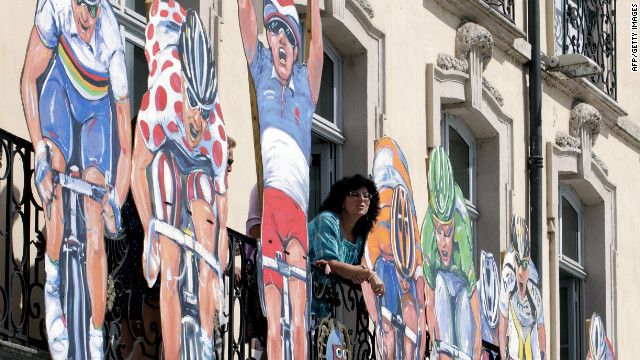 Large cutouts of cyclists in colorful jerseys are featured on the facade of a building in Macon on Wednesday.