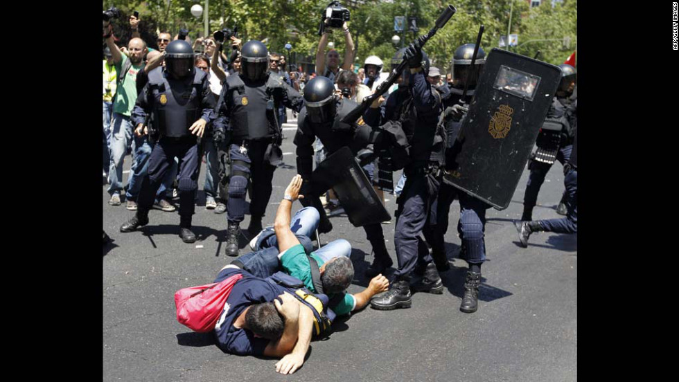 Riot police advance on two downed protesters on Wednesday, Jully 11, in Madrid, as clashes erupt during demonstrations against Spain's government and its cuts to curb the country's debt crisis.