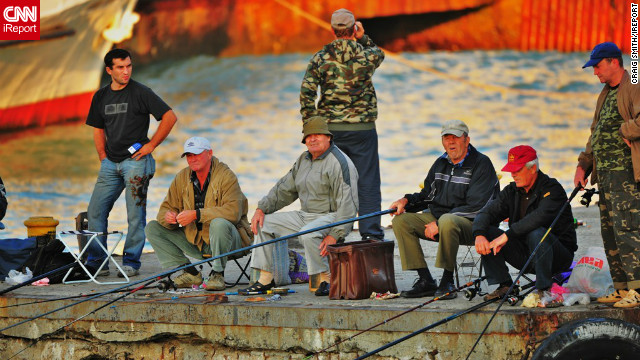 "This image of a group of men fishing on a crumbling pier was captured by Craig Smith in the southern harbor city of Odessa. ""I wanted to capture .... the coastline as well as the friendly people who we met on the streets,"" he says."