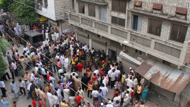 Pakistani residents and rescuers gather outside the police hostel after an attack on prison guards in Lahore on Wednesday.