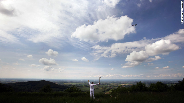 Torchbearer Eugene Perry carries the Olympic flame at Sutton Bank in the North Yorkshire Moors National Park in York, England, on June 20.