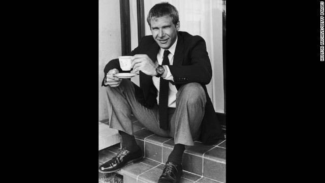 Harrison Ford sits on steps, smiling while holding a teacup and saucer.