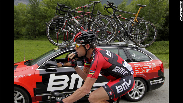 Australia's Cadel Evans checks technical problems with his radio-link earphones as he rides on Friday.