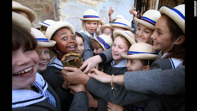 Schoolgirls outside Salisbury Cathedral on Thursday hold the torch carried by retired sprinter and four-time gold medal winner Michael Johnson.