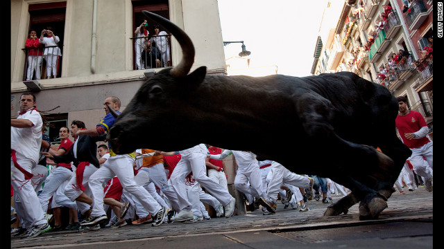 Revelers run beside a Don Juan Pedro Domecq fighting bull on Friday at Curva Estafeta.