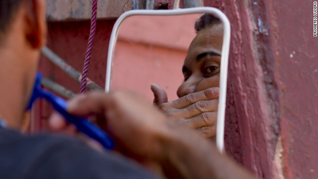 An immigrant shaves outside the shelter, taking a break after days as a stowaway on a cargo train heading north.