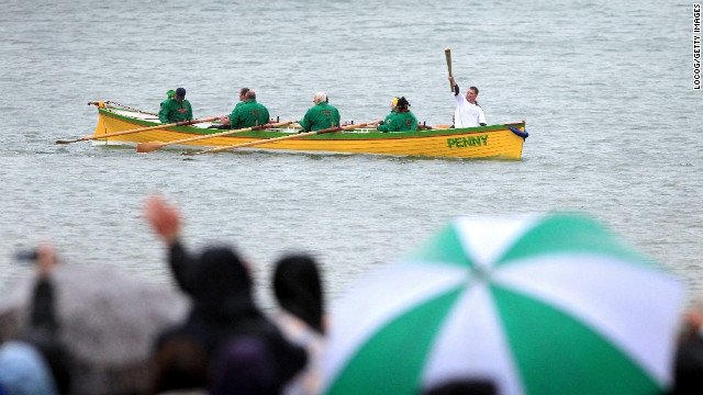 Ryan Hope carries the torch Thursday, July 12, on the row boat Penny off the waters of Weymouth.