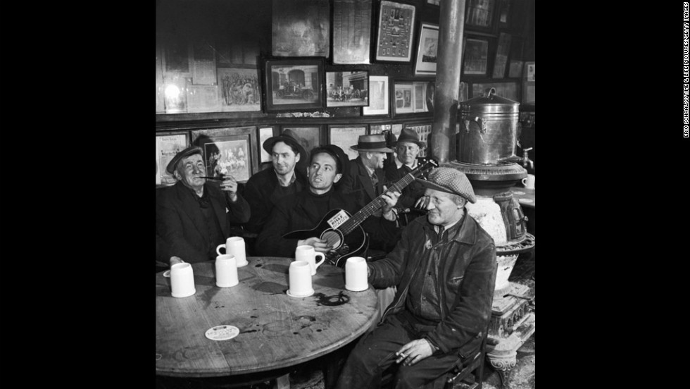"In 1943, when these photos were taken in New York City, Woody Guthrie was still relatively unknown outside of musical circles, but his semi-fictionalized biography, ""Bound for Glory,"" would soon introduce him to a wider audience, and in the coming years his influence on folk and protest music would become profound. This photo was taken at McSorley's Old Ale House, which still stands today in the East Village. Guthrie was born in Oklahoma on July 14, 1912. He died in New York in 1967 at age 55. <!-- --> </br>"