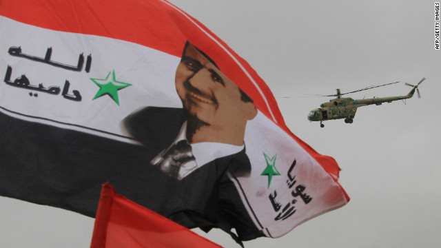 A Syrian army helicopter hovers above a national flag bearing a portrait of Syrian President Bashar al-Assad on January 11, 2012.