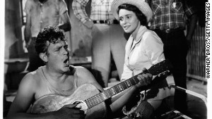 Andy Griffith plays guitar as Patricia Neal watches in a scene from the 1957 film \