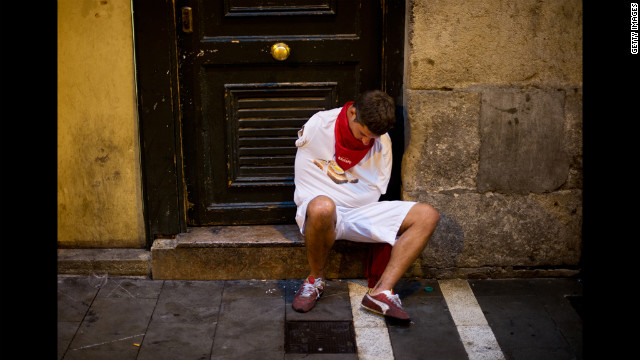A man sleeps at the entrance of the bullring before the next run starts.