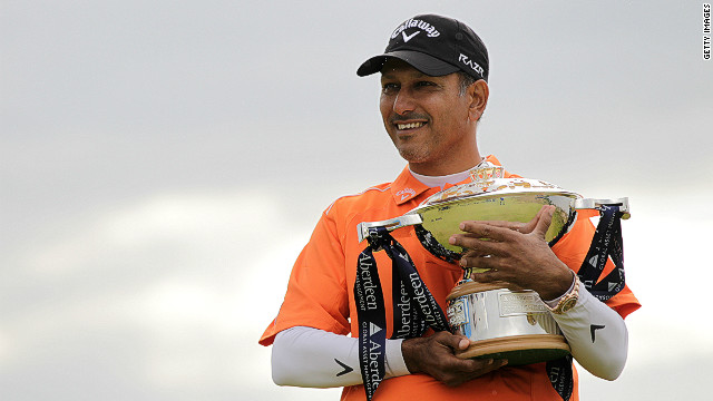 Jeev Milkha Singh cradles the Scottish Open trophy after beating Italy's Francesco Molinari in a playoff on Sunday