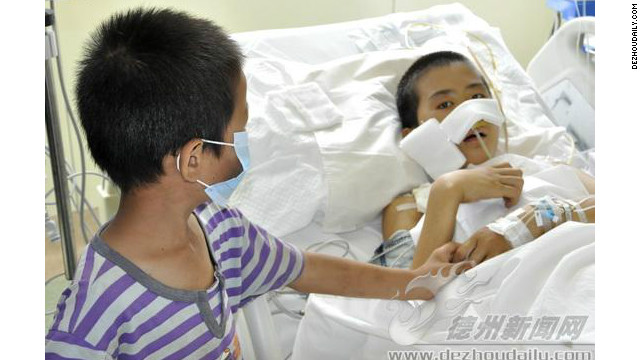Du Chuanwang lies in the hospital with his younger brother by his side.